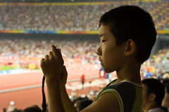 Boy takes a picture at Olympic games. BEIJING, CHINA - AUGUST 16, 2008: Profile of a young boy spectator taking a picture with his digital camera in Birds Nest Royalty Free Stock Photography