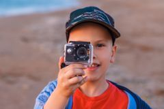 The boy takes pictures on action camera.  Stock Photos