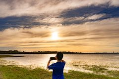 A boy is taking pictures of the sunset royalty free stock photo