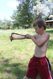 Boy taking aim from a slingshot towards. Boy in red shorts. The background forest Stock Photos