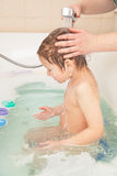 Boy taking bath. Little boy taking bath, hands of his mother washing his head Royalty Free Stock Image
