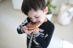 The boy is taking a bite. A big bite of a delicious donut by a small boy stock photo