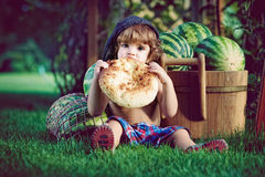 Boy taking a bite of the bread. Little boy sitting on the grass near the pile of watermelons bite the big cake. Closeup portrait in retro style royalty free stock photos