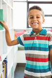Boy taking a book from bookshelf in library Stock Image