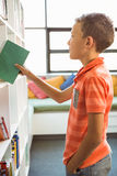 Boy taking a book from bookshelf in library Royalty Free Stock Photos