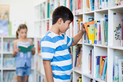 Boy taking a book from bookshelf in library Stock Photography