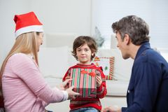 Boy Taking Christmas Present From Mother Stock Image