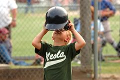 Boy Taking Off Batting Helmet. Young boy taking off batting helmet in little league baseball game Stock Photo