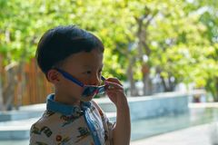 Boy is taking off sunglasses while in travelling trip stock image