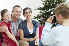 Boy Taking Photo Of Family By Christmas Tree. Young boy taking photo of sitter; mother and father by Christmas tree Stock Image