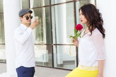 Boy taking photo of his beautiful girlfriend on Stock Image