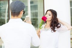 Boy taking photo of his girlfriend on phone camera Stock Photos