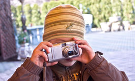 Boy taking photograph. Young boy with woolly hat and obscured face taking photograph with digital camera outdoors Stock Photos