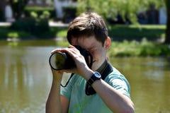 Boy taking photos. Teenager boy with a digital reflex camera taking photos Royalty Free Stock Photos