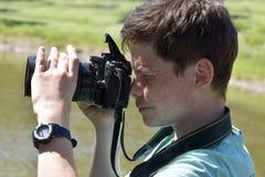 Boy taking photos. Teenager boy with a digital reflex camera taking photos Stock Photography