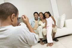 Boy Taking Picture of Family on sofa. In living room Stock Photography
