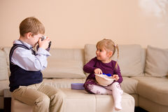 Boy taking picture of his sister Royalty Free Stock Image