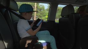 Boy taking pictures with cell when traveling by car. Boy taking mobile photos of a town when traveling by car. He sitting on back seat with safety belt stock video