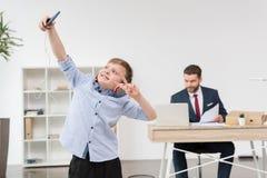 Boy taking self portrait while his father businessman stock photos