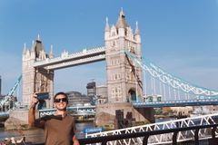Young man taking selfie in London with Tower Bridge on background royalty free stock photos