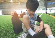 Boy taking shoes off ready for soccer training ground. Boy taking shoes off getting ready for soccer training ground Stock Photography