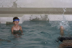 Boy taking a swim lesson. A boy taking a swim lesson at an indoor pool Royalty Free Stock Image
