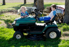 Boy talk and a riding mower Royalty Free Stock Photos