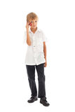 A boy talking on a cell phone. A boy wearing a white shirt talking on a cell phone Royalty Free Stock Images