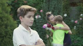 Little boy presents a flowers to mother, the eldest son was upset. The boy is talking with his mother in the garden on blurred background. Youngest son brings a stock video