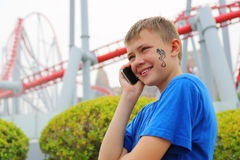 Boy talking on a mobile at an amusement park Stock Photos