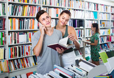 Boy talking on mobile phone while buying books with friend in st Stock Photo