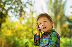 Boy talking on mobile phone. Cute little boy talking on mobile phone in summer park Royalty Free Stock Image