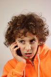 A boy is talking on the phone. A young boy is talking on the phone  with a mockery gesture Stock Photography