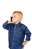 Boy talking on phone. Cute little boy talking on phone in denim blue shirt isolated on white background Stock Images