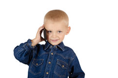 Boy talking on phone. Cute little boy talking on phone in denim blue shirt isolated on white background Royalty Free Stock Images
