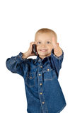 Boy talking on phone. Portrait of a cute smiling little boy talking on phone with thumb up in denim blue shirt isolated on white background Stock Photos