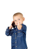 Boy talking on phone. Portrait of a cute smiling little boy talking on phone with thumb up in denim blue shirt isolated on white background Stock Image