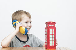 Boy talking on the phone and red telephone booth Stock Photo