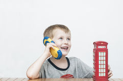 Boy talking on the phone and red telephone booth Stock Images