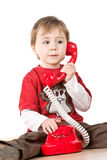 Boy talking on red phone Stock Image