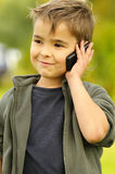 Boy talking to a cell phone Stock Images