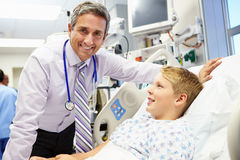 Boy Talking To Male Consultant In Emergency Room. Looking At Camera Smiling royalty free stock photography