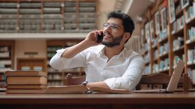 Boy Talks on Phone in Library. Intelligent male student talking on phone in large library, handsome bearded boy wearing pristine white shirt and glasses, using stock footage