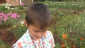 The boy talks and shows berries of a raspberry in bucket. The boy talks and shows berries of a raspberry in a small bucket stock video footage