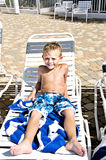 Boy Tanning. Young cute boy laying on a lounge chair getting a sun tan Stock Photo