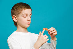 Boy tapping adhesive plaster on his hand Stock Photo