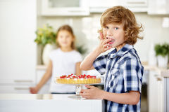 Boy tasting from cake at birthday Royalty Free Stock Photography