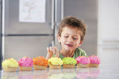 Boy Tasting Cupcakes At Home Royalty Free Stock Image