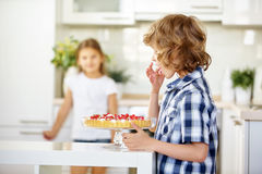 Boy tasting from fruit cake with currants Stock Photo