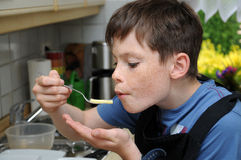 Boy tasting noodles Stock Photo